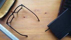 Table de bureau avec les verres, l'ordinateur portable, le téléphone, le carnet et la règle Photographie stock