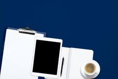 Table de bureau de travail de bureau avec l'ordinateur portable, le comprimé, la tasse de café et le carnet vide sur le fond bleu Images stock