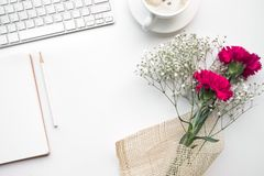 Table de bureau de siège social avec le bloc-notes, bouquet de fleur Photos stock