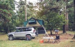 Table de camping et outre du véhicule routier dans le terrain de camping Image libre de droits