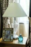 Table de chevet avec la lampe et le cadre de tableau Photo stock