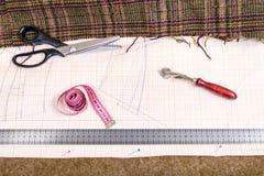 Table de coupe avec le tissu, modèle, travaillant des outils Photos libres de droits
