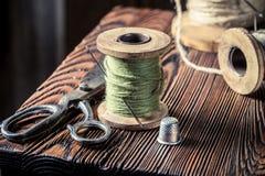 Table de couture avec des ciseaux, des fils et l'aiguille Photographie stock libre de droits