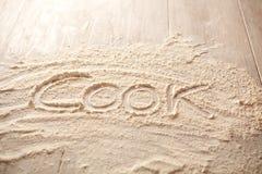 Table de cuisine avec de la farine et le cuisinier de mot écrit là-dessus photographie stock libre de droits