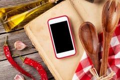 Table de cuisine avec des ingrédients, des ustensiles et le téléphone images libres de droits