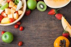 Table de cuisine avec la variété du cadre de fruits, salade de fruits sur le bois Photographie stock