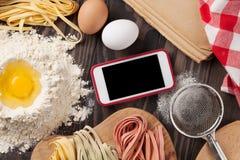 Table de cuisine avec le smartphone, les ustensiles et les ingrédients photo stock