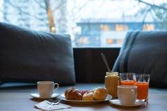 Table de cuisine foncée avec l'ensemble de petit déjeuner Croissant, beurre d'arachide et café fraîchement cuits au four sur le c images stock