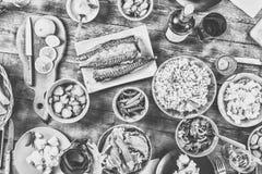 table de dîner Amis heureux à la table de dîner avec les divers casse-croûte, préparations pour les hot-dogs faits maison, tintan Photographie stock