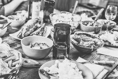 table de dîner Amis heureux à la table de dîner avec les divers casse-croûte, préparations pour les hot-dogs faits maison, tintan Photos stock