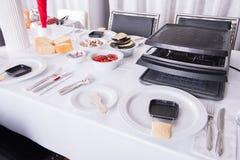 Table de dîner préparée pour le raclette avec des amis Photos libres de droits