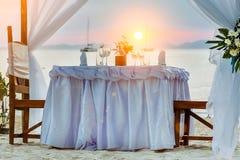 Table de dîner romantique sur la plage tropicale, pendant le coucher du soleil, bateaux en mer sur le fond photos libres de droits