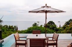 Table de dîner de station de vacances de relaxation de vacances par la mer de piscine d'infini photographie stock libre de droits