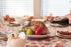 Table de dîner de vacances avec la dinde rôtie, homme versant le vin rouge dans le premier plan photographie stock libre de droits