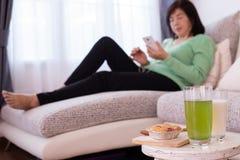 Table de dessert avec la belle fille à la maison utilisant le smartphone sur le divan, concept de soins de santé photographie stock