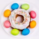 Table de fête avec les oeufs et le petit gâteau colorés Photo stock