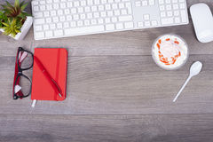 Table de fonctionnement avec le clavier, les notes, le stylo, les verres et la crème glacée i Photographie stock