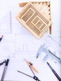 Table de fonctionnement d'architecte avec le modèle de maison de plan et l'instrum d'écriture Images stock
