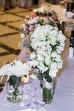 Table de mariage avec des bouquets avec les roses blanches Images stock