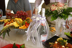 Table de mariage Deux ont décoré des bouteilles de champagne, de fruits et de bouquet du ` s de jeune mariée Photos libres de droits