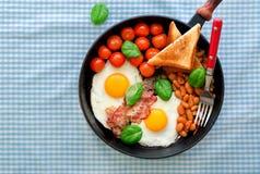 Table de petit déjeuner avec l'oeuf au plat, les haricots, les tomates, le lard et le pain grillé Image stock