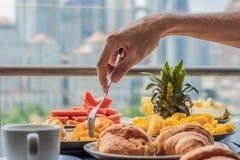 Table de petit déjeuner avec le fruit et le pain de café croisant sur un balcon contre le contexte de la grande ville Photos stock