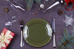 Table de portion de Noël - plat, verre, lampe, bougie, cônes de pin, boîte-cadeau Vue supérieure Fond rustique avec l'espace de t Image stock