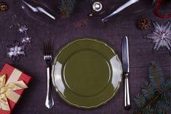 Table de portion de Noël - plat, verre, lampe, bougie, cônes de pin, boîte-cadeau Vue supérieure Fond rustique avec l'espace de t Images libres de droits