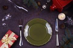 Table de portion de Noël - plat, verre, lampe, bougie, cônes de pin, boîte-cadeau Vue supérieure Fond rustique avec l'espace de t Photos libres de droits