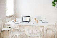 Table de réunion avec les ordinateurs portables et le café dans la pièce vide de bureau Images libres de droits