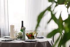 Table de salle à manger avec, champagne, bougies et salade, ensemble pour le dîner d'anniversaire photos stock