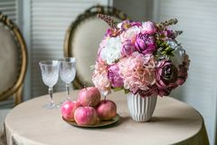 Table de salle à manger avec les chaises classiques, un bouquet d'hortensia et de pivoines dans un vase, verres de vin et pommes photos stock