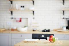 Table de salle à manger avec les pommes fraîches dans la cuvette photo stock
