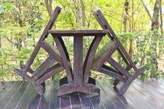 Table de salle à manger en bois mise dans l'arrangement de jardin luxuriant Photographie stock