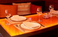 Table de salle à manger en verre avec le contre-jour orange Photo libre de droits