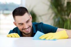 Table de sourire de nettoyage d'homme avec le tissu à la maison Images libres de droits