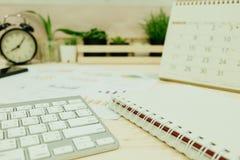 Table de travail avec le clavier, papier vide de carnet, calendrier, infos g Images libres de droits