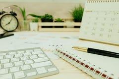 Table de travail avec le clavier, stylo, papier de carnet, graphique d'infos, horloge Photo stock