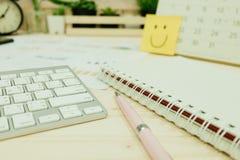 Table de travail avec le clavier, stylo, papier de carnet, graphique d'infos, horloge Image libre de droits