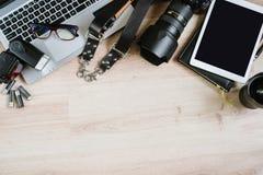 Table de travail de hippie de photographie mise avec l'ordinateur, le comprimé, le film, les lentilles, les approvisionnements et Photographie stock libre de droits