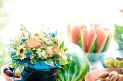 Table de vacances de portion avec des bouquets des marguerites et du fruit Photo libre de droits