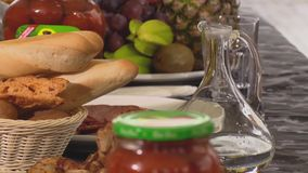 Table with decanter, baguette, fried chiken, salami and fruits stock footage