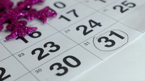 On the table is the December calendar of the New Year hand draws a pencil on the date of December 31, close-up, the new