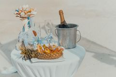 Table decorated with bottle of champagne, cooler, glasses and fruits Royalty Free Stock Photos