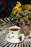 Table decorated with flowers and a cup of tea at an outdoor cafe Royalty Free Stock Images