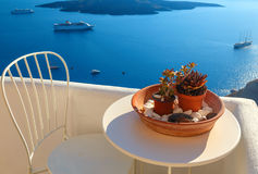 Table decorated with flowers on terrace overlooking sea and cruise ships in Fira, Santorini, Cyclades, Greece Royalty Free Stock Photo