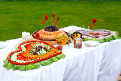 Table decorated with hearts of fruit and sausages Stock Photos