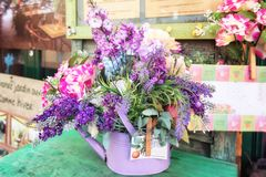 Table decorated with a purple watering can filled with artificial flowers in all kinds of shades of purple