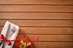 Decorated table with red gift and hearts for special event. Table decorated with red and golden gift for special event and planked wood table background. Top Stock Image