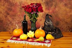Table decorated with red rug, autumn flowers, bottle of wine, witch hat, pumpkins and squashes Royalty Free Stock Image